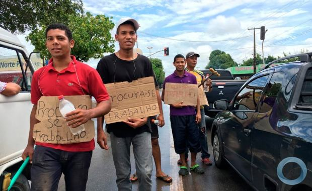"Venezuelans show signs saying ""looking for jobs"" to drivers in Roraima, Brazil"