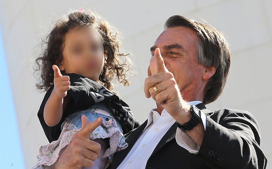 Jair Bolsonaro, candidate for Brazilian presidency, teaches a child his infamous gesture of a gun